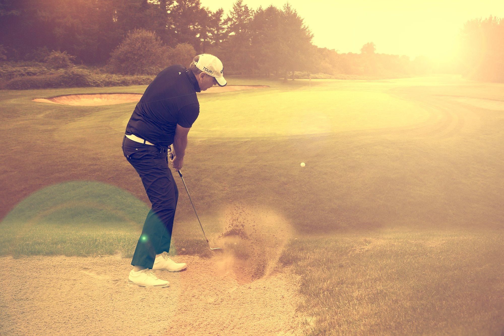 Golfspieler schlägt aus dem Sand